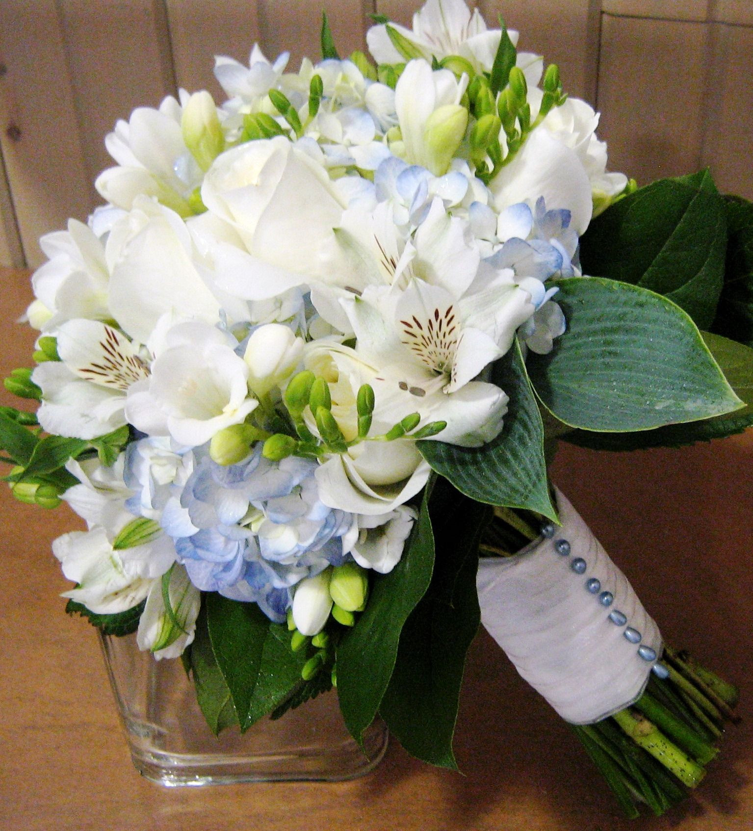 Bridal Bouquet with blue hydrangea white freesia alstroemeria and import roses JG I really the hint of blue in it and the light green is this possible