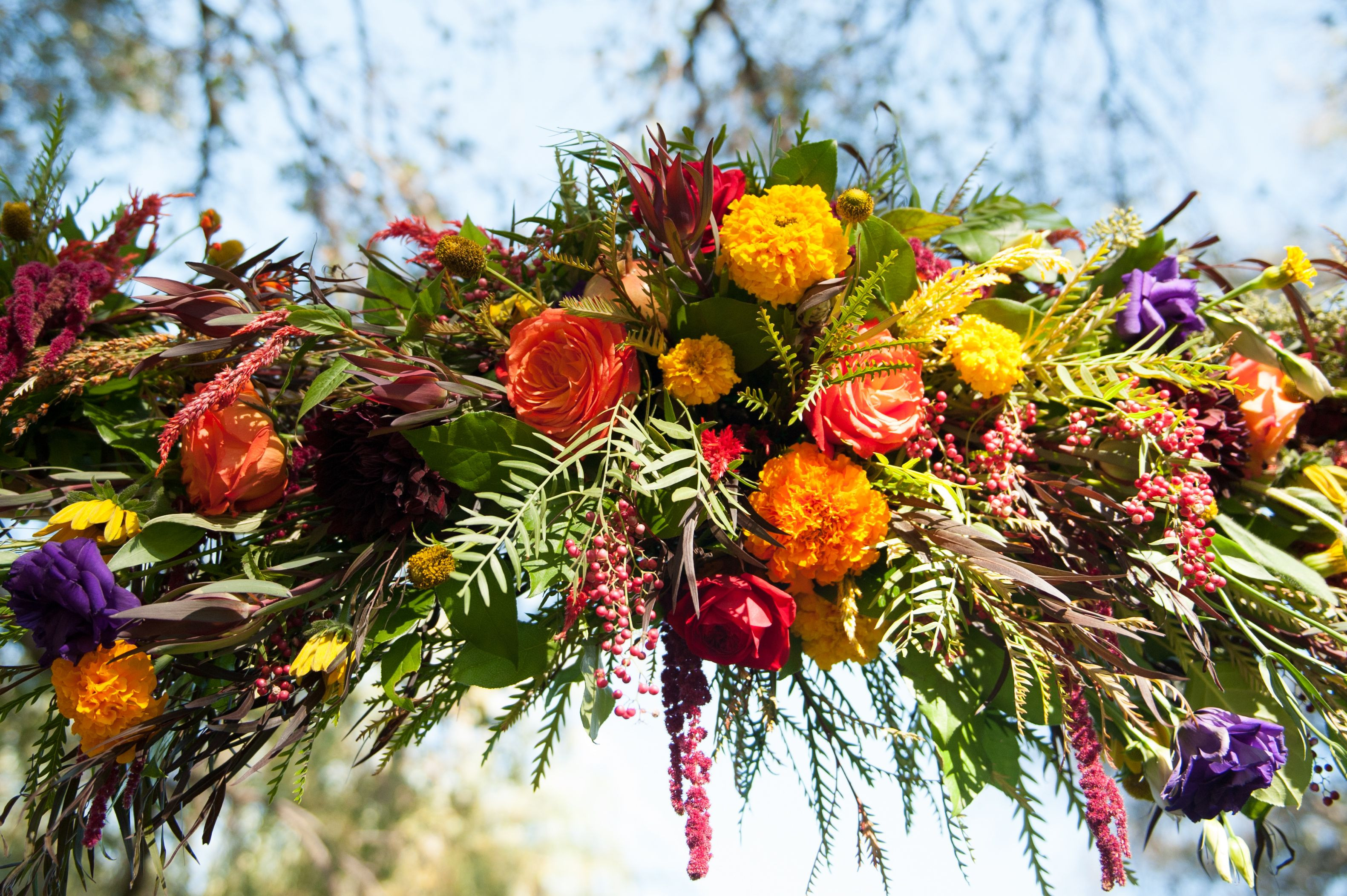Flowers in this arch pieces include Marigolds roses lisianthus amaranthus pepper berries
