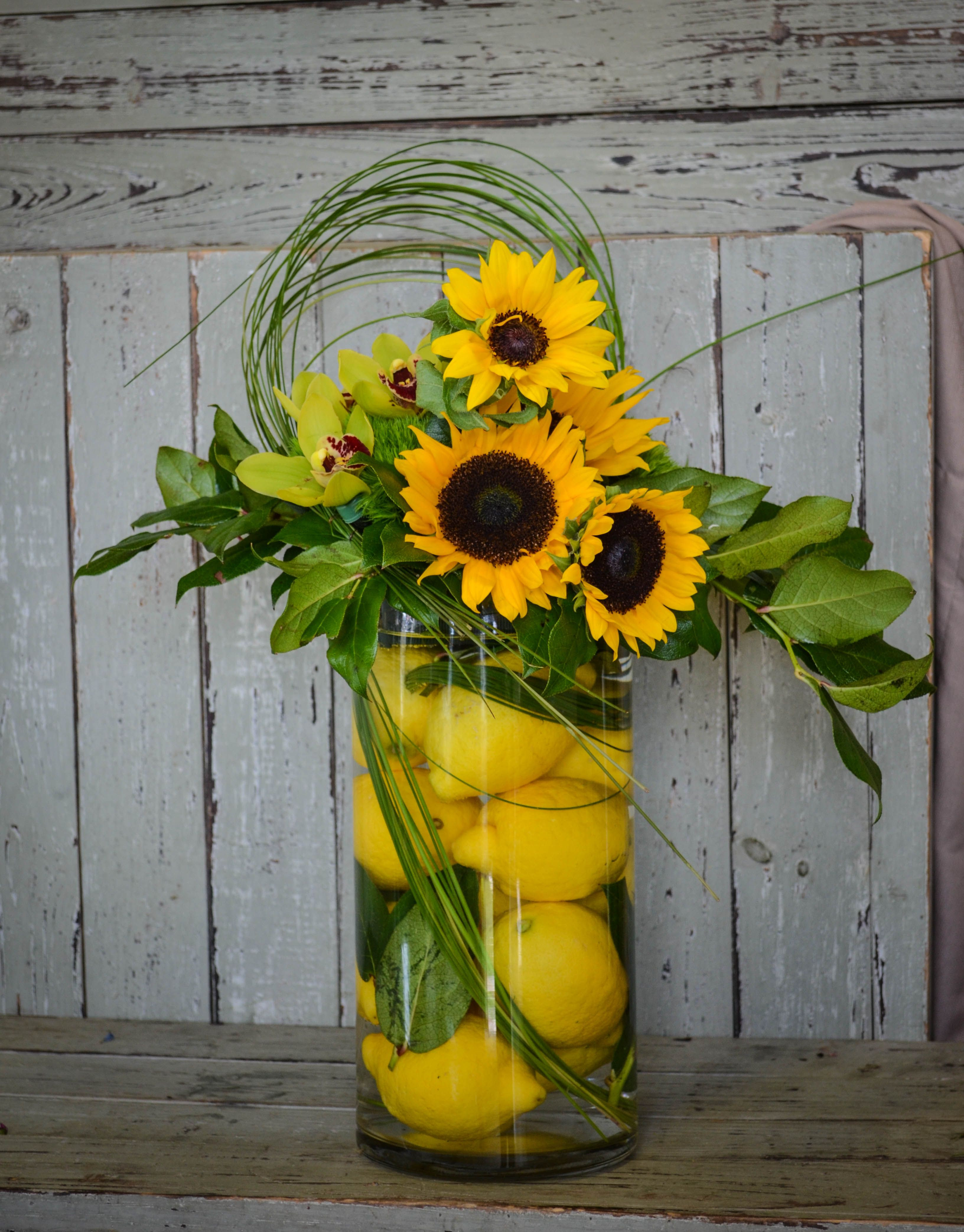 Lemons sunflowers and orchids with bear grass in a cylinder vase Elegant & cheerful