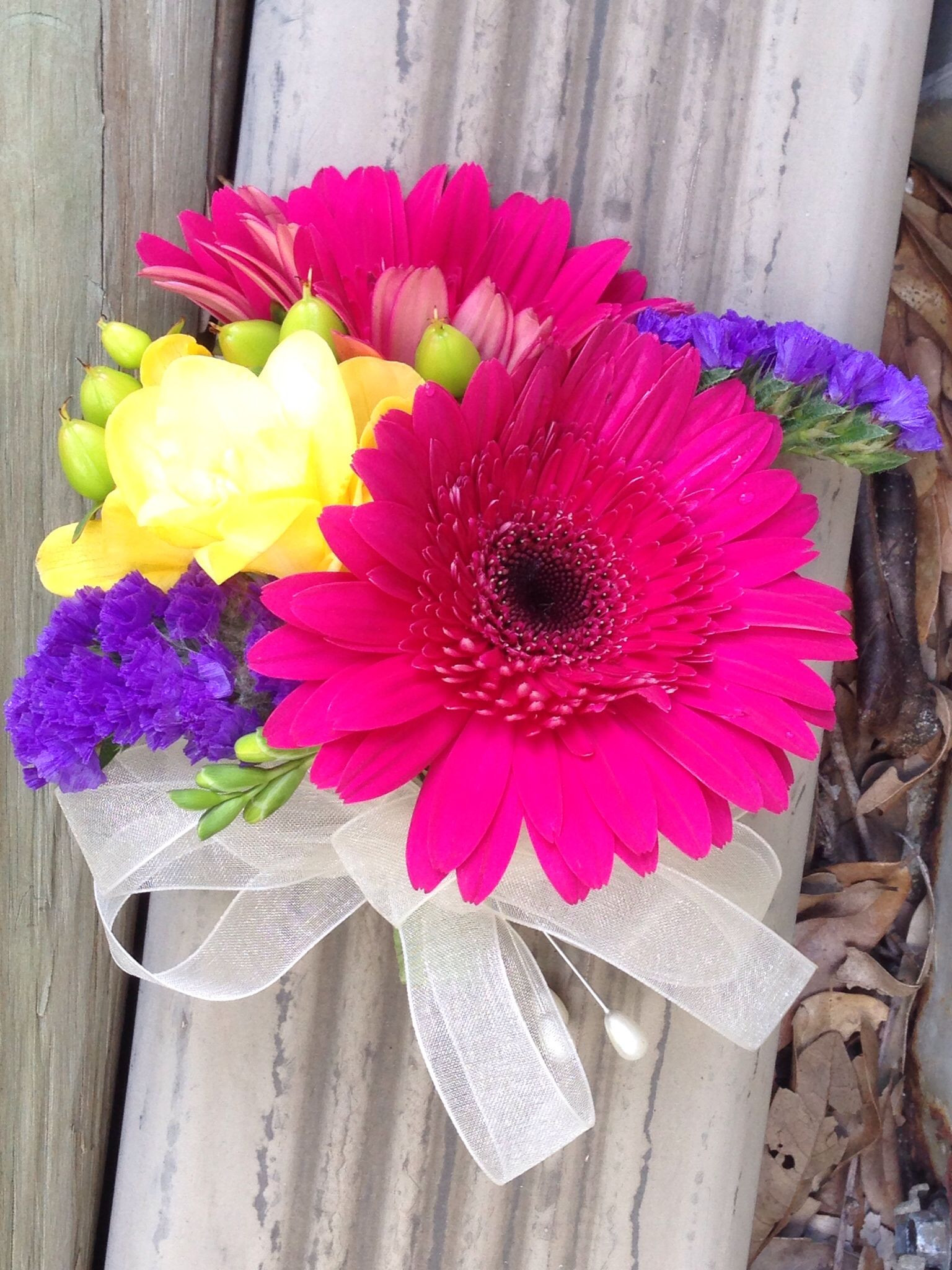 Gerbera Daisies in Hot Pink Corsage with Yellow Freesia and Purple Statice Accents