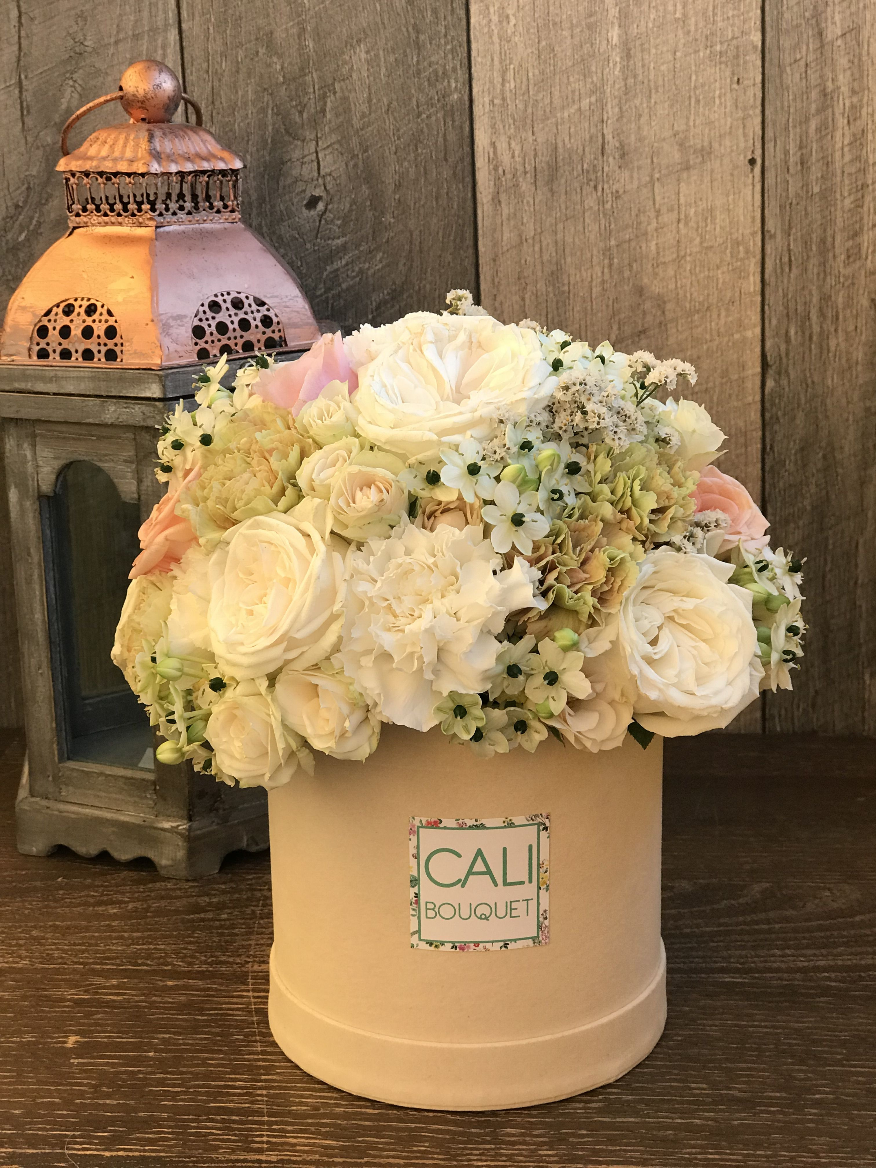 Soft pale roses carnations and other flowers in 4—4 inch beige hat box by Cali Bouquet So beautiful It makes the perfect t