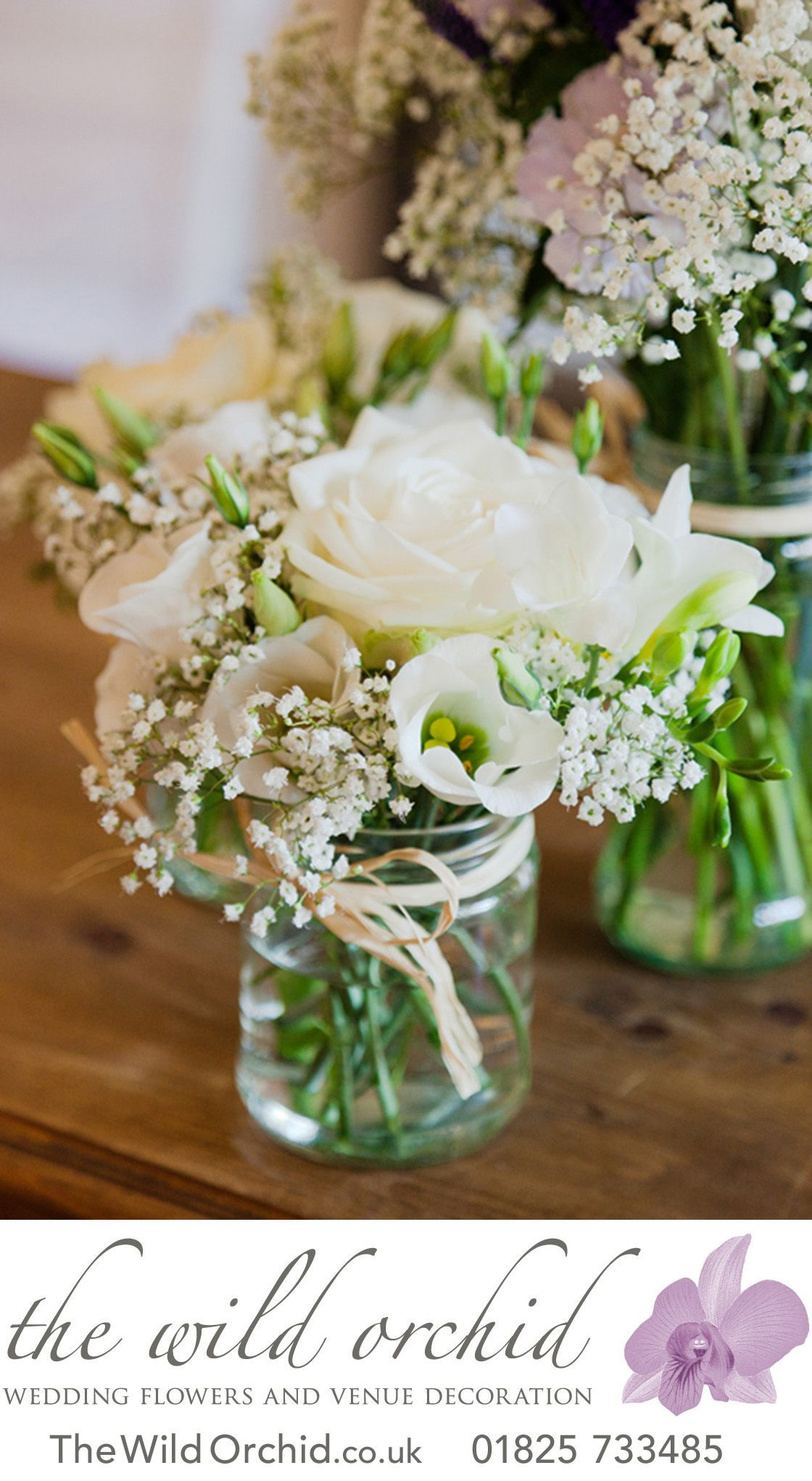 A trio of clear glass jam jars with natural raffia ribbon filled with delicate white flowers with touches of blue