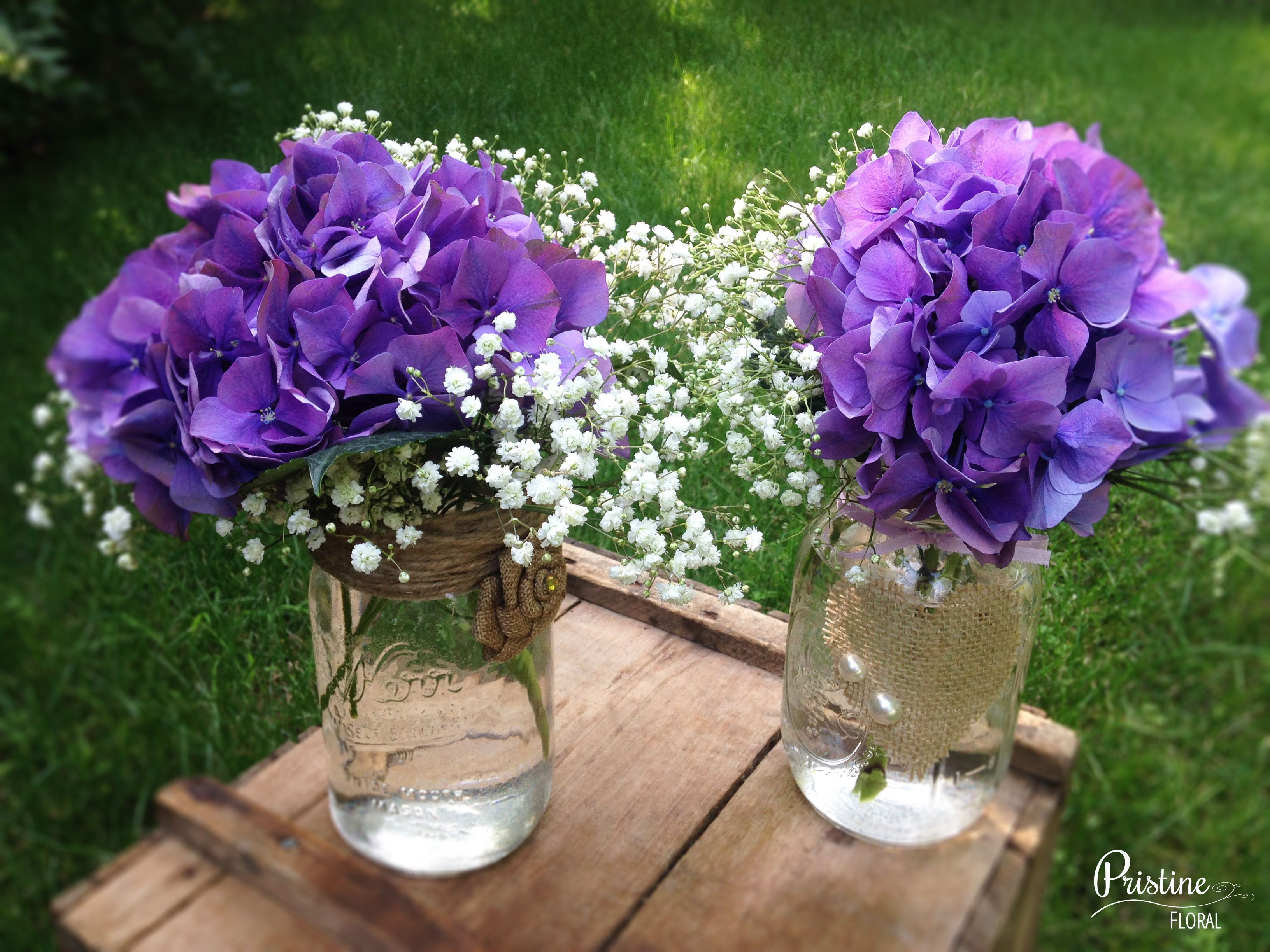 Rustic Mason Jar Centerpieces designed with Purple Hydrangea finished with Baby s Breath More