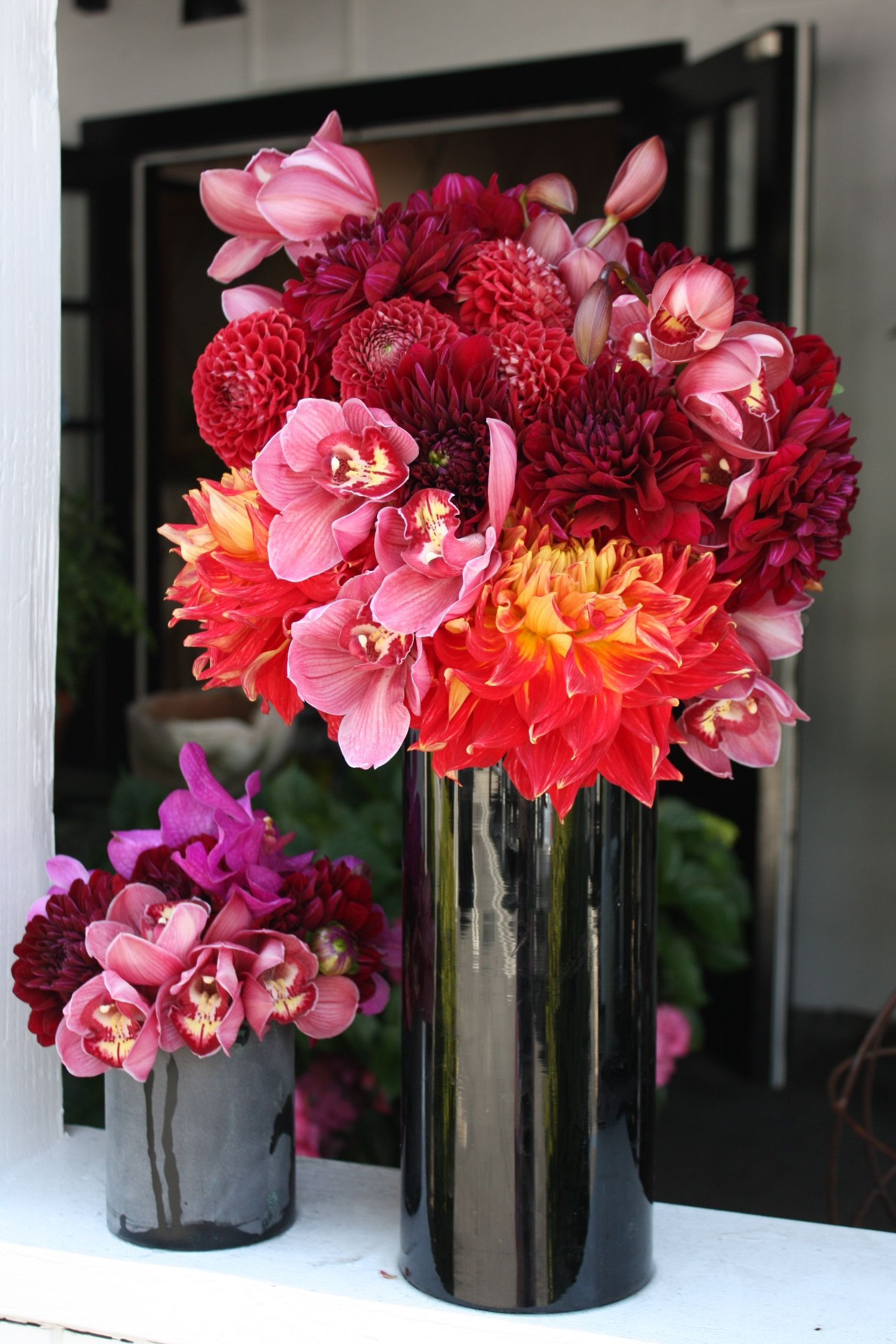 """This dramatic black vase is offset with orange """"dinner plate"""" dahlias deep red dahlis and mauve cymbiduym orchids by Botany Flowers"""