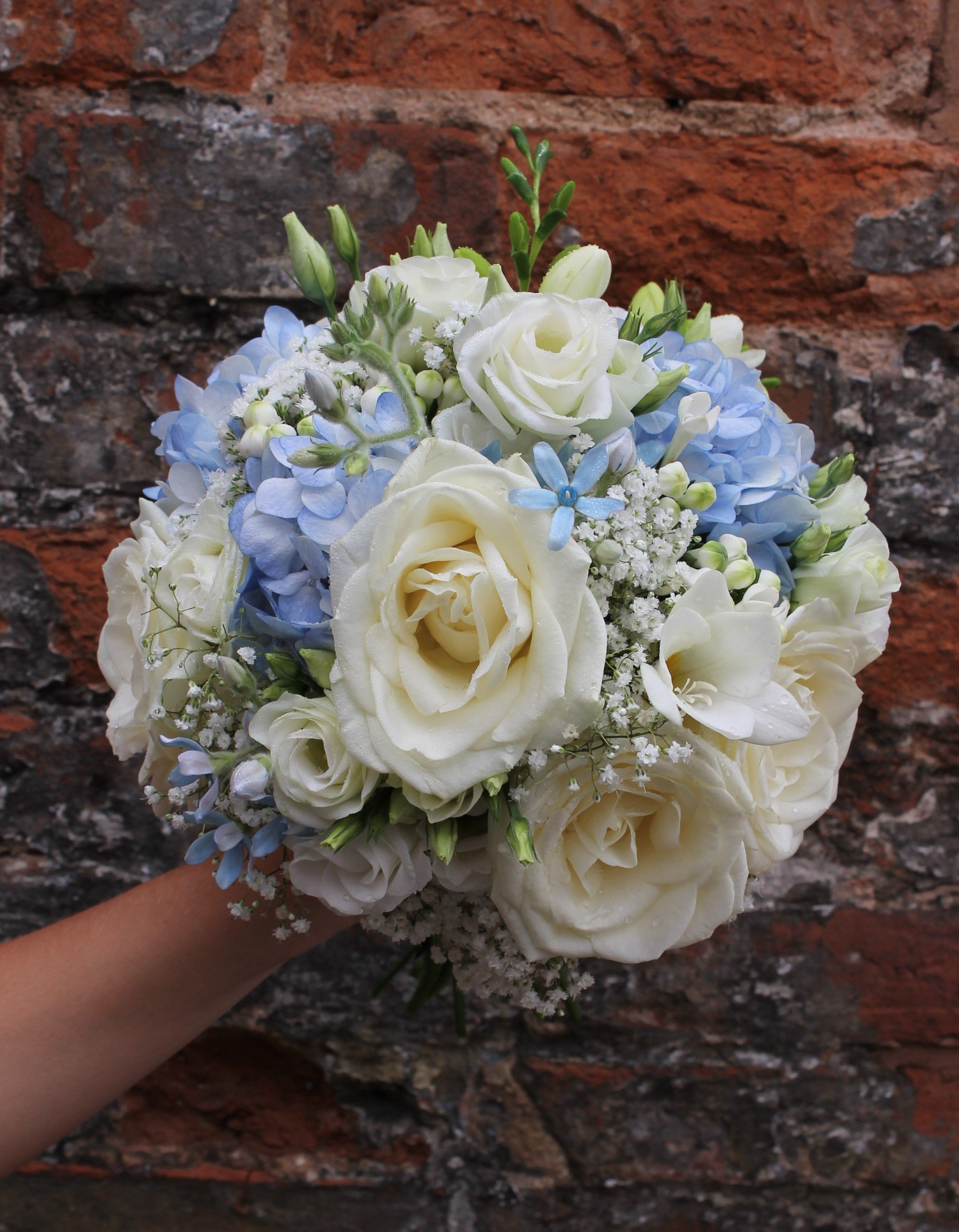 bridesmaid s bouquet hand tied design pale blue and ivory flowers delphinium hydrangea avalanche rose oxypetalum gypsophila freesia and