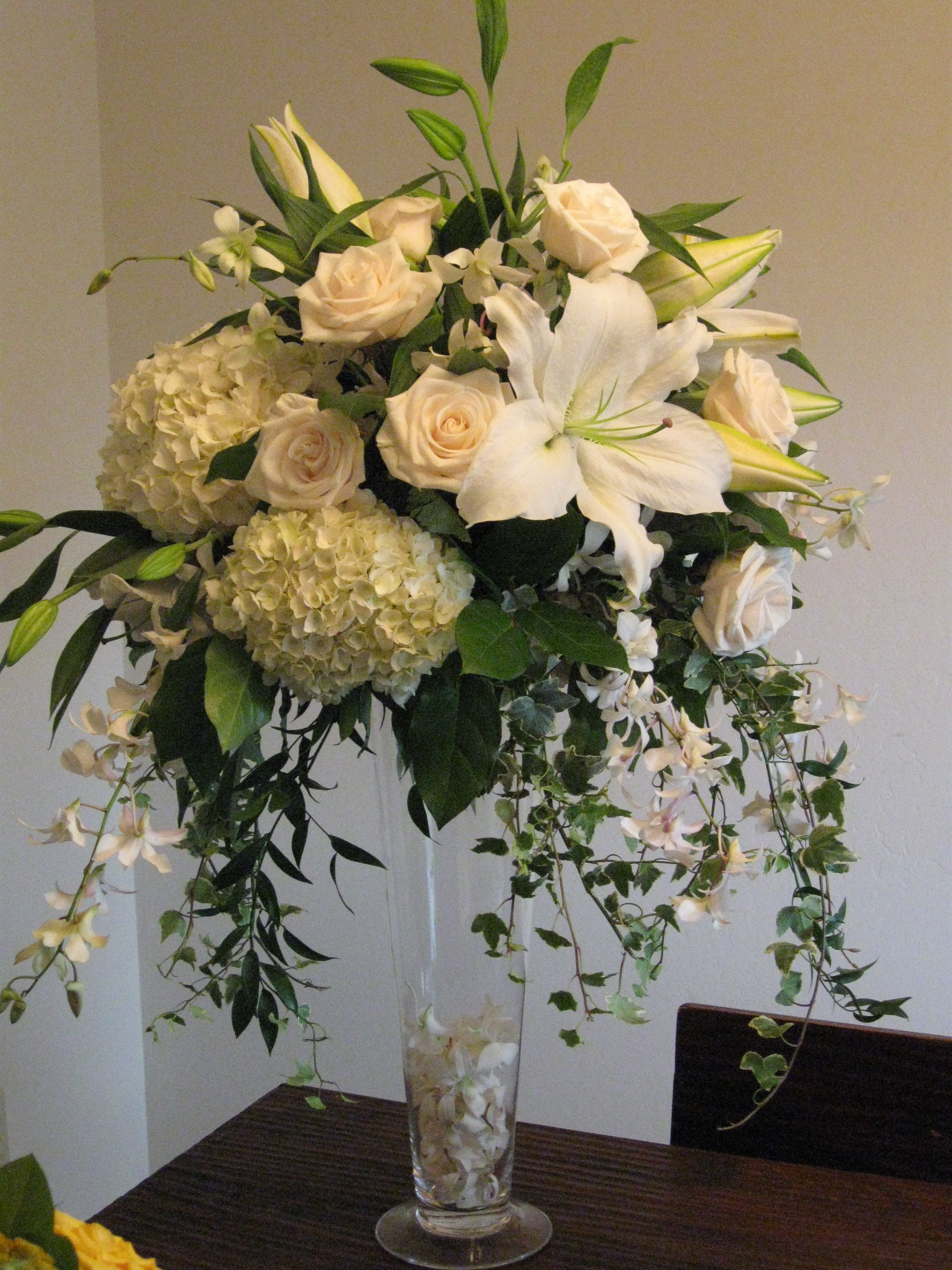 Centerpiece white Roses Hydrangea Orchids Tall Vendela The blue orchid Dendrobium Ivy Casablanca Oriental lilies Trumpet vase