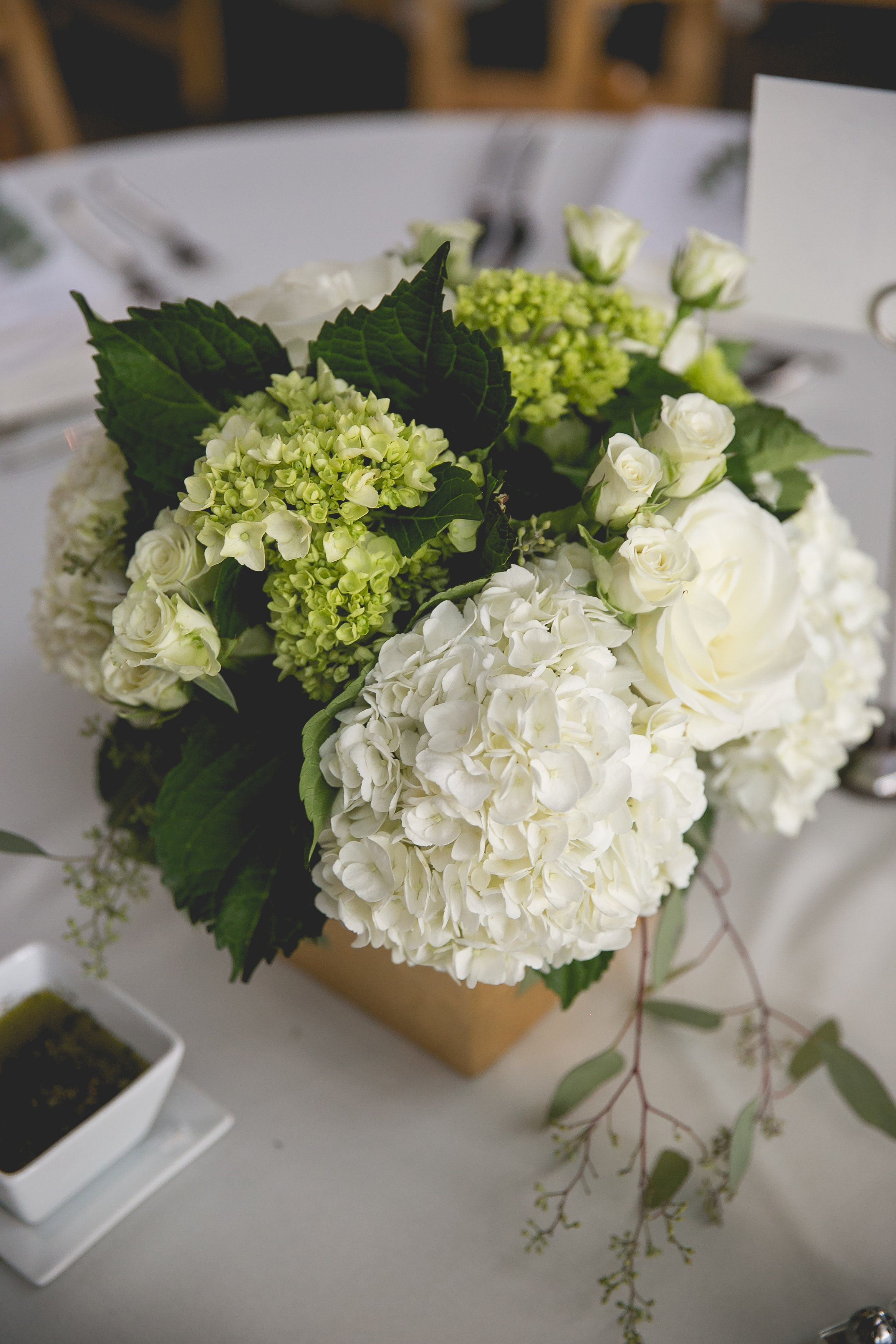 Green and white hydrangea with seeded eucalyptus and spray rose filler Flowers by Regalo Design