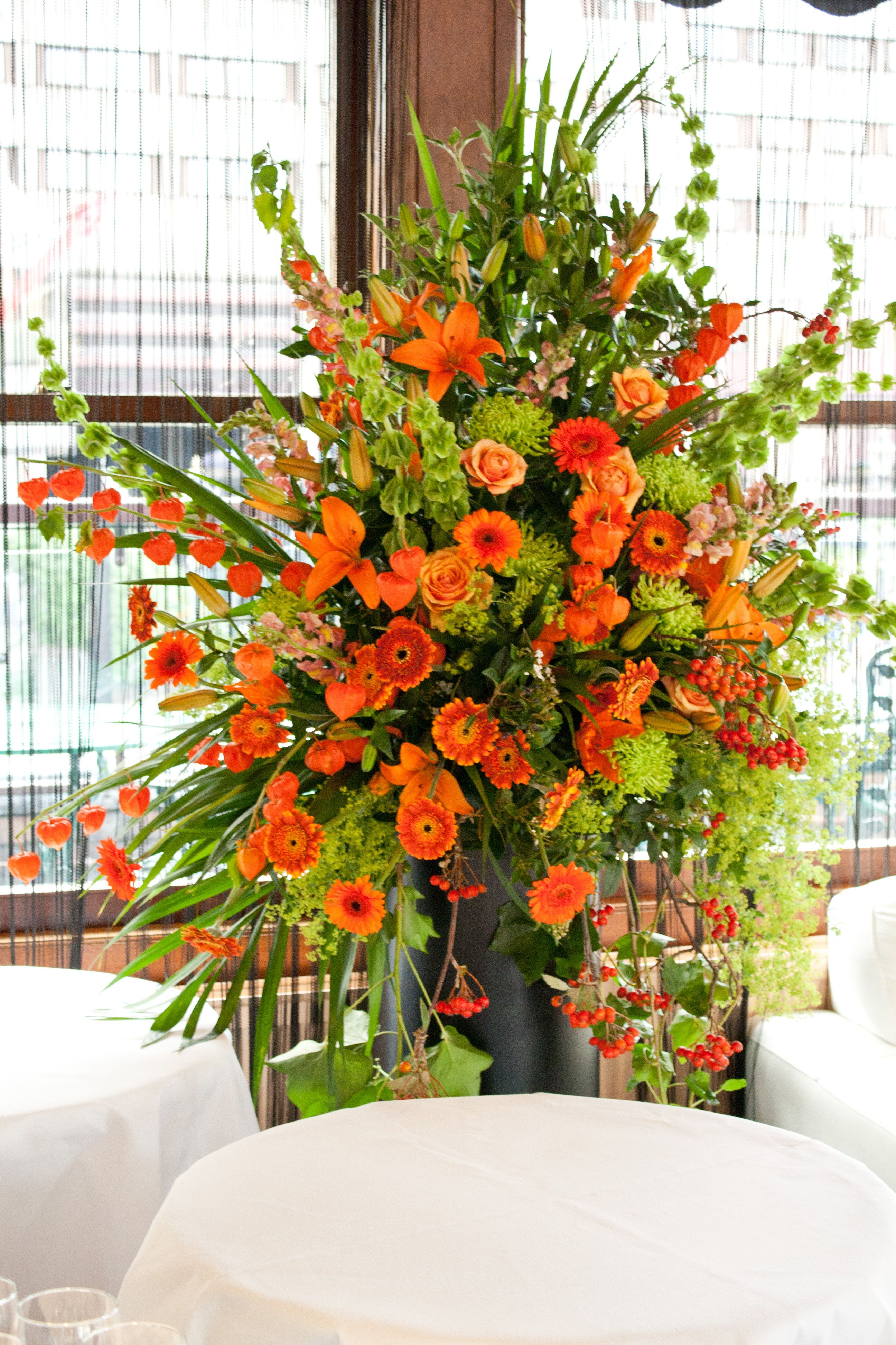 Orange and lime green flower pedestal arrangement suitable to decorate the reception church ceremony