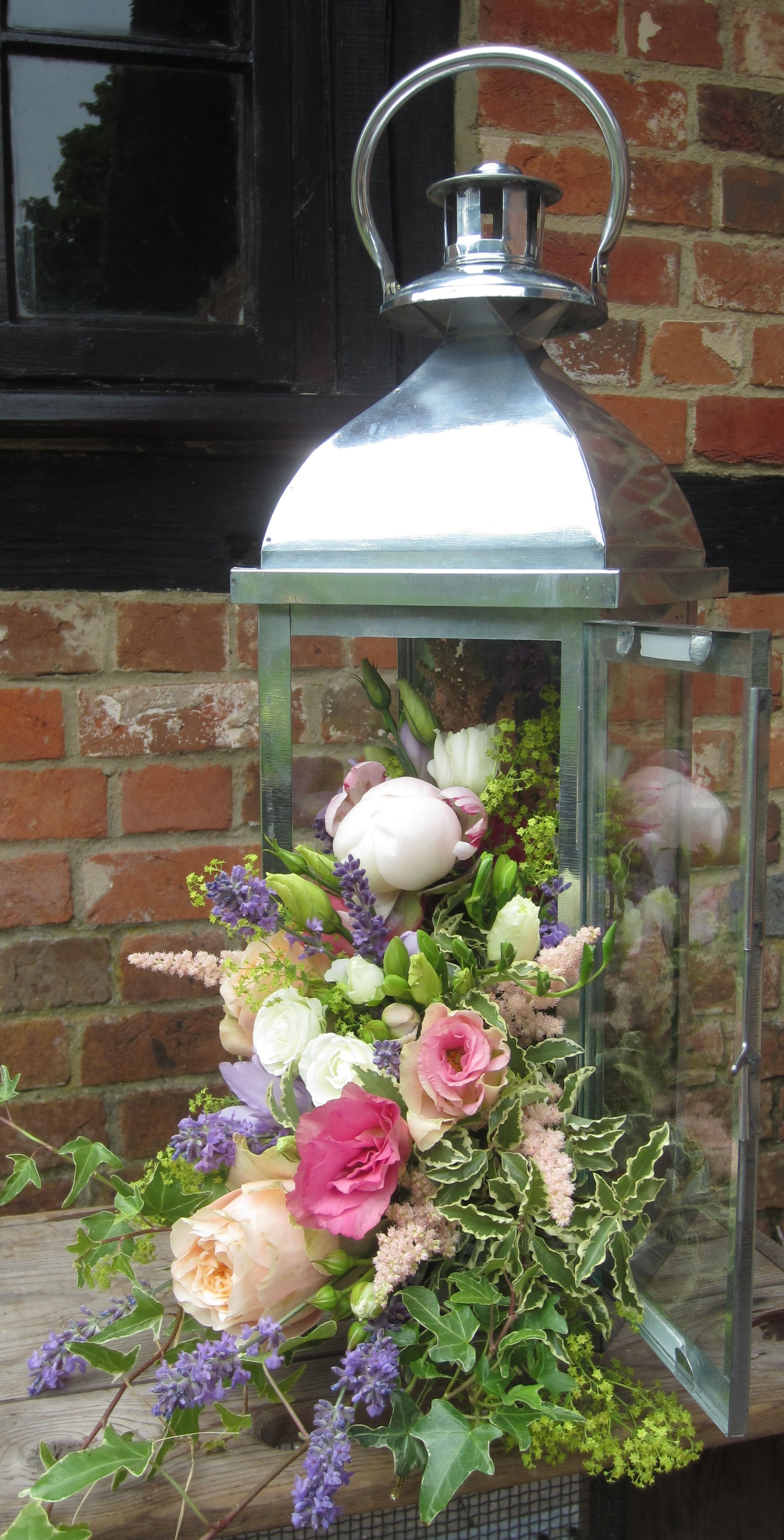 Lantern with cascading flowers including pale pink peony vuvuzela roses peach lisianthus cream spray roses lavender ivy and achillea mollis Bury