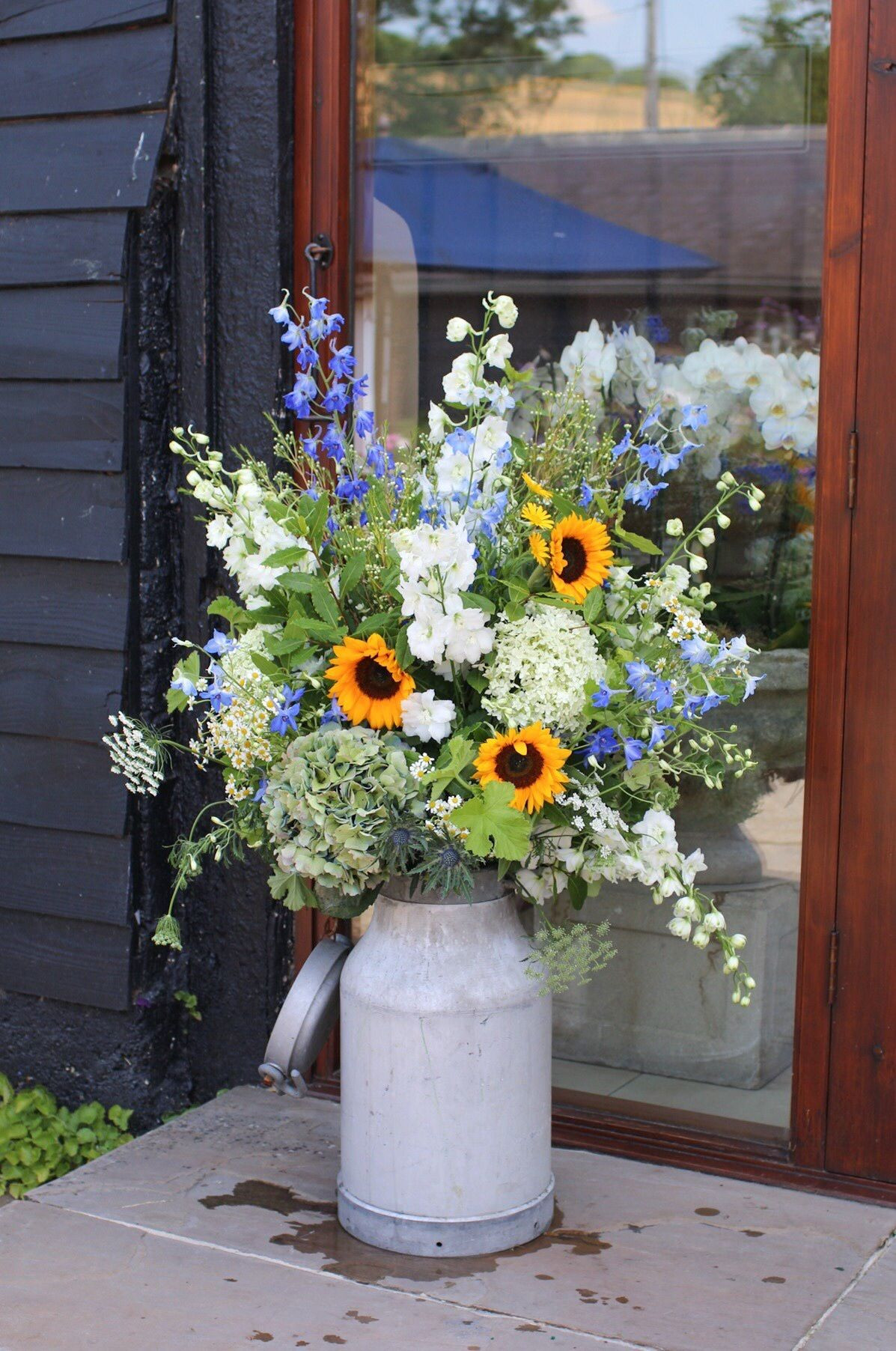 Milk churn arrangements on either side of the ceremony room doors Sunflowers delphiniums and hydrangeas cottage flowers