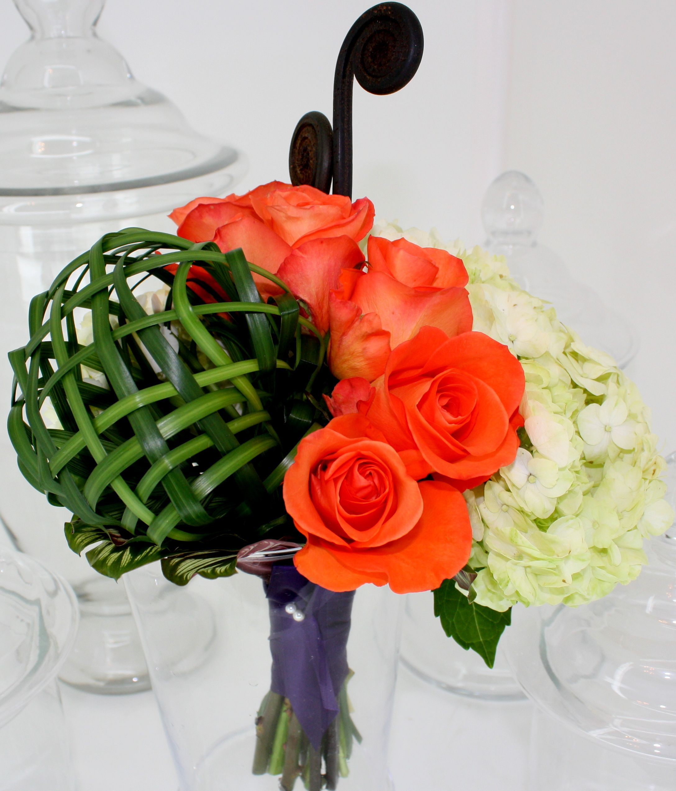 This contemporary bridal bouquet features a weaved lily grass sphere orange unique roses hydrangea and a couple of fiddle heads
