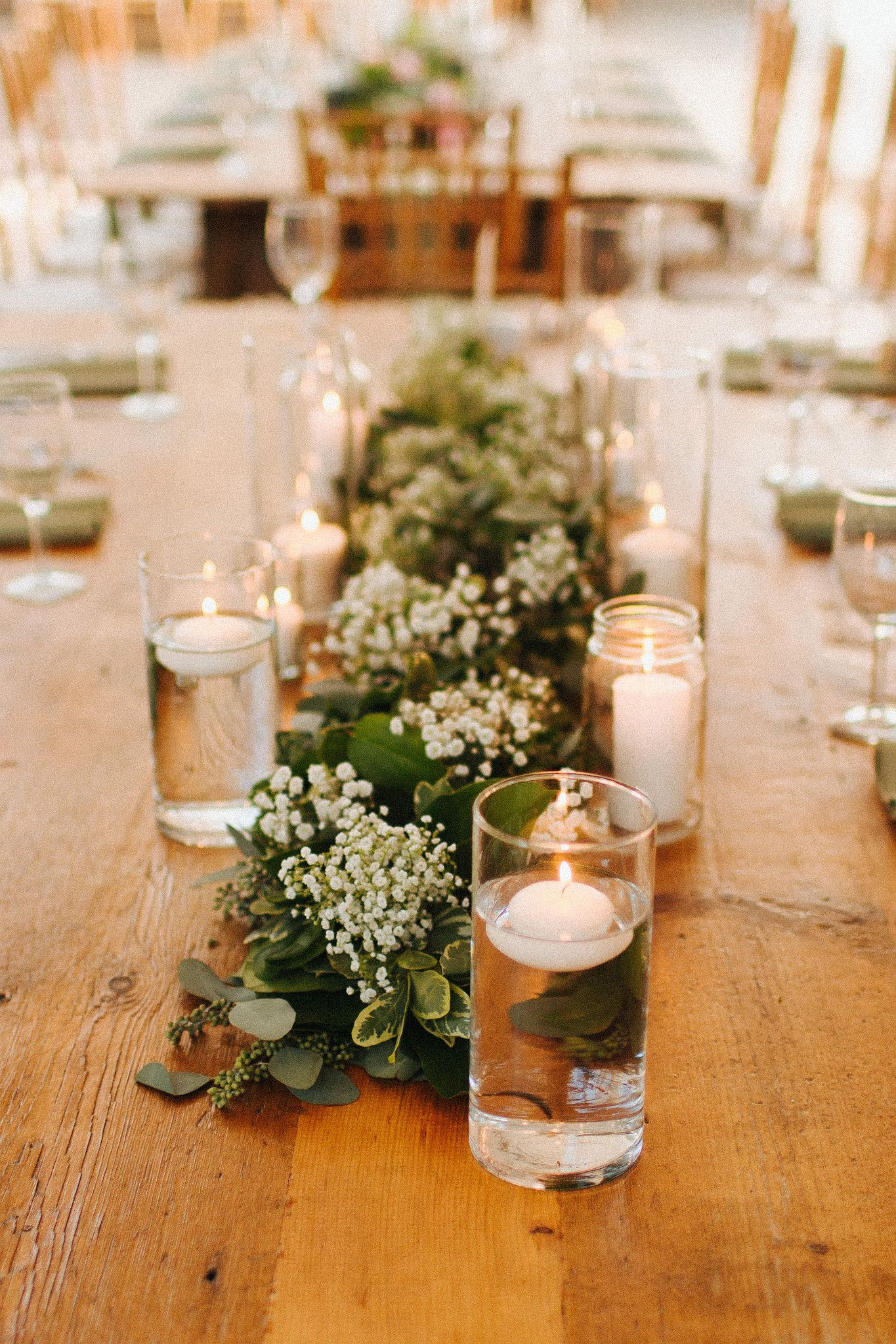 Floating candles and lush greenery runners with babies breath pair perfectly with Buttercup s rustic farm tables at Elizabeth and Mickey s Anthony Wayne