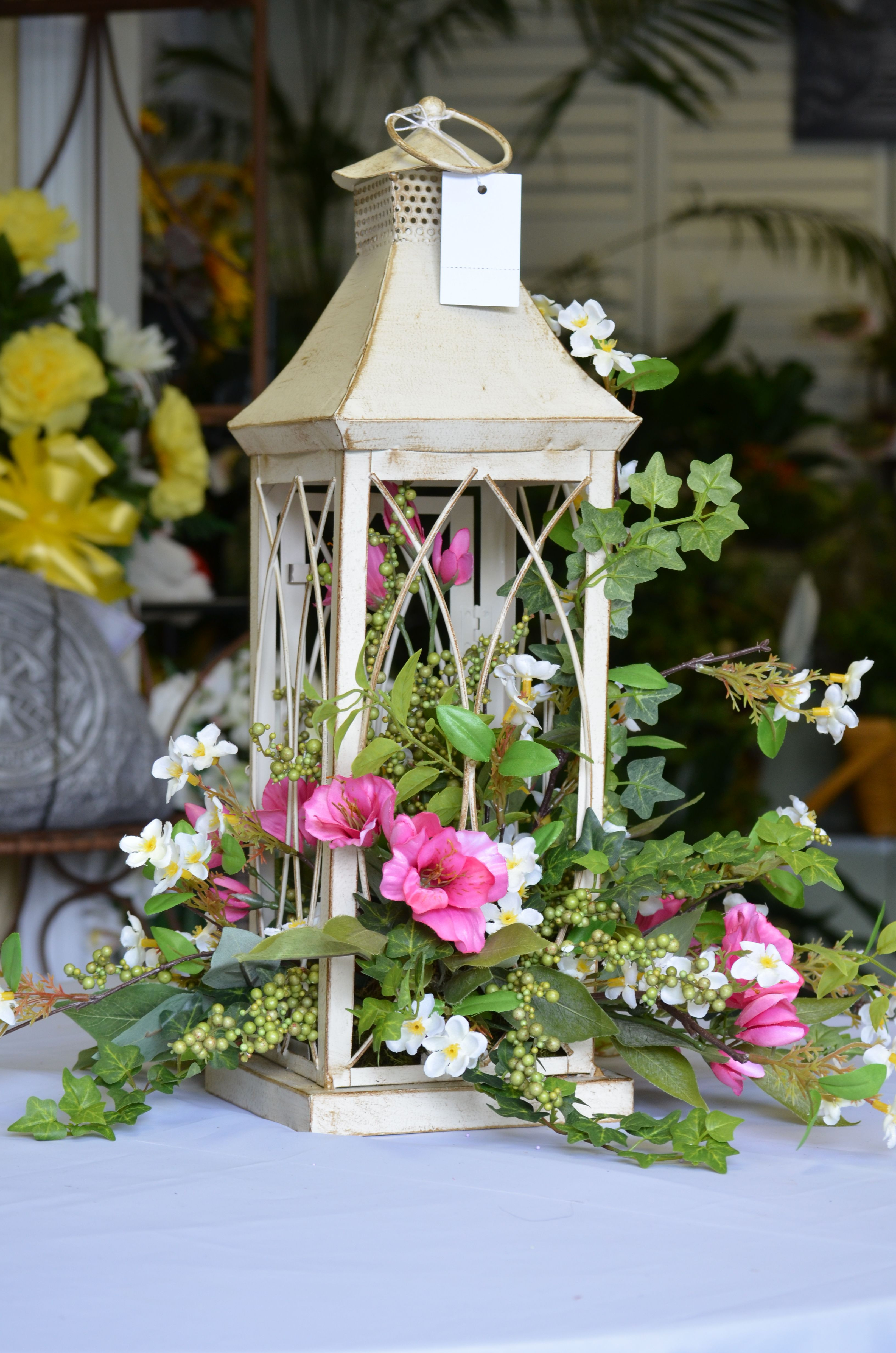 """A delightful silk arrangement in a lantern Never thought about allowing the flowers to """"spill"""" out of the lantern"""