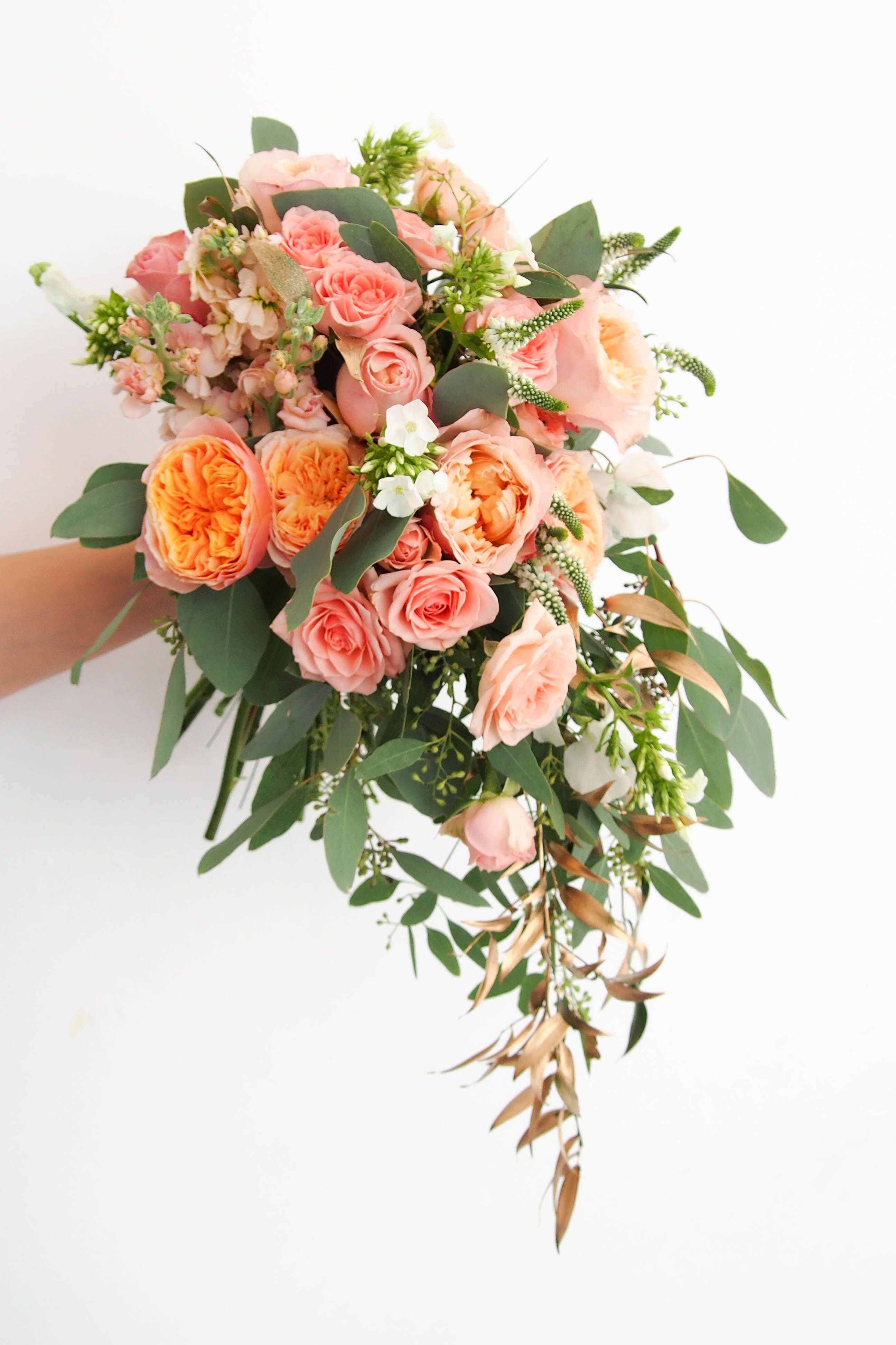 garden rose vuvuzela in a cascading waterfall bridal bouquet with gold ruscus eucalyptus and spray roses by floral magic