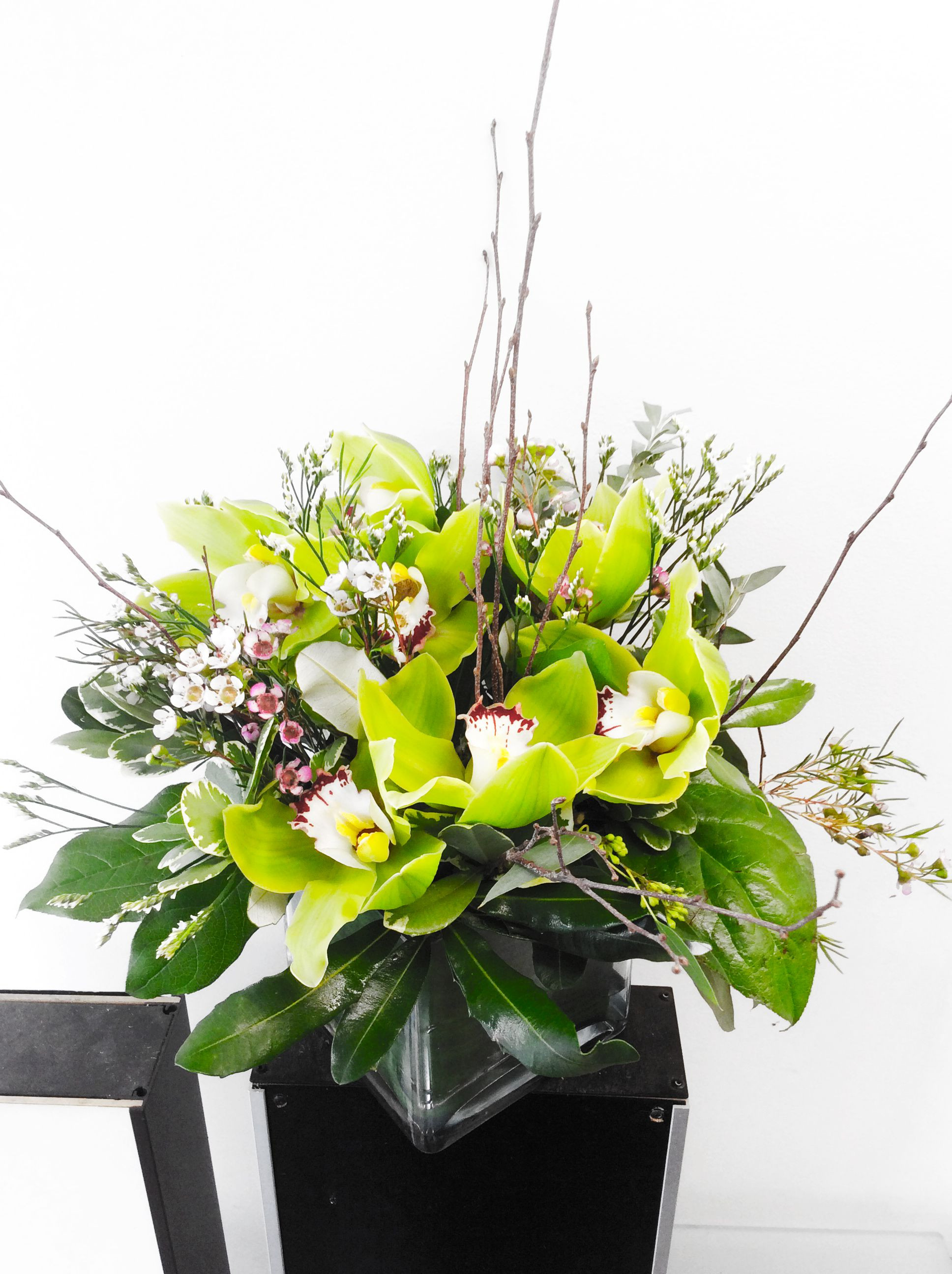 A custom floral arrangement in a square vase designed by Flowers Naturally in NYC green cymbidium orchid white & pink wax flower white