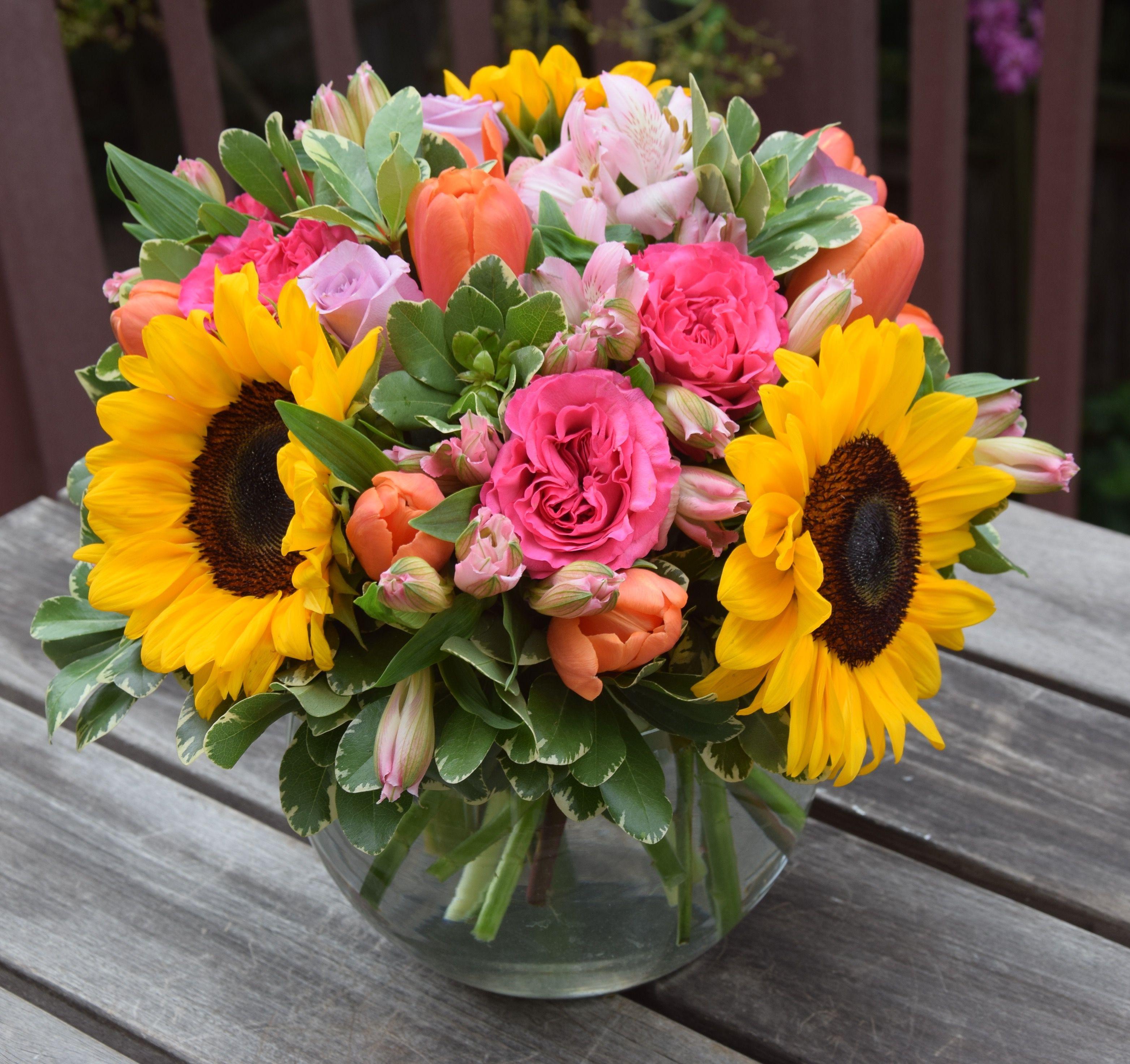 Flower arrangement with sunflowers garden roses tulips alstroemerias