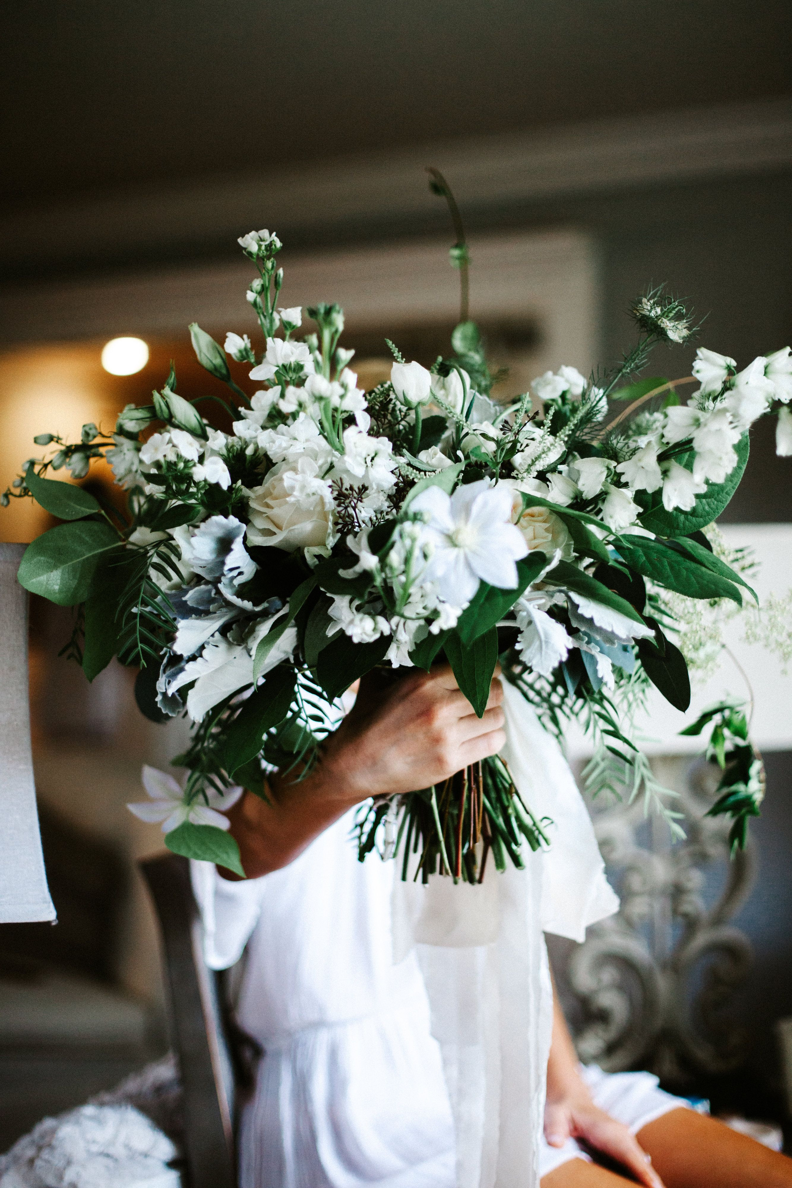 just delivered loose and organic hand tied bridal bouquet of white clematis white and ivory roses white delphinium white larkspur white stock