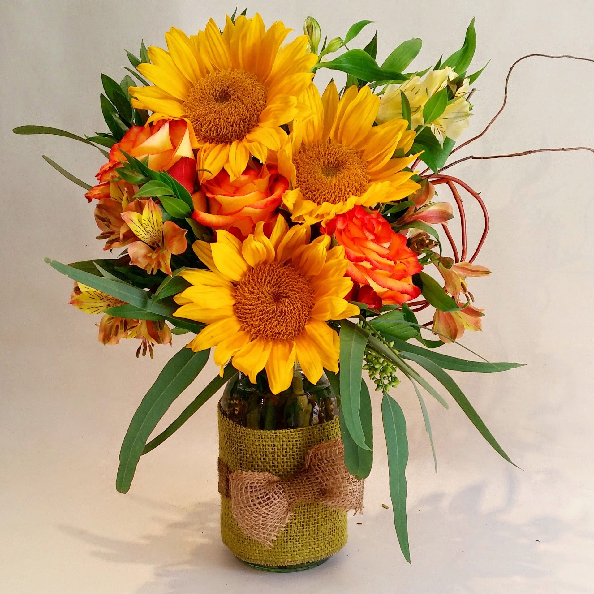 Totally cute and happy sunflowers in a mason jar decorated with burlap wrap and bow