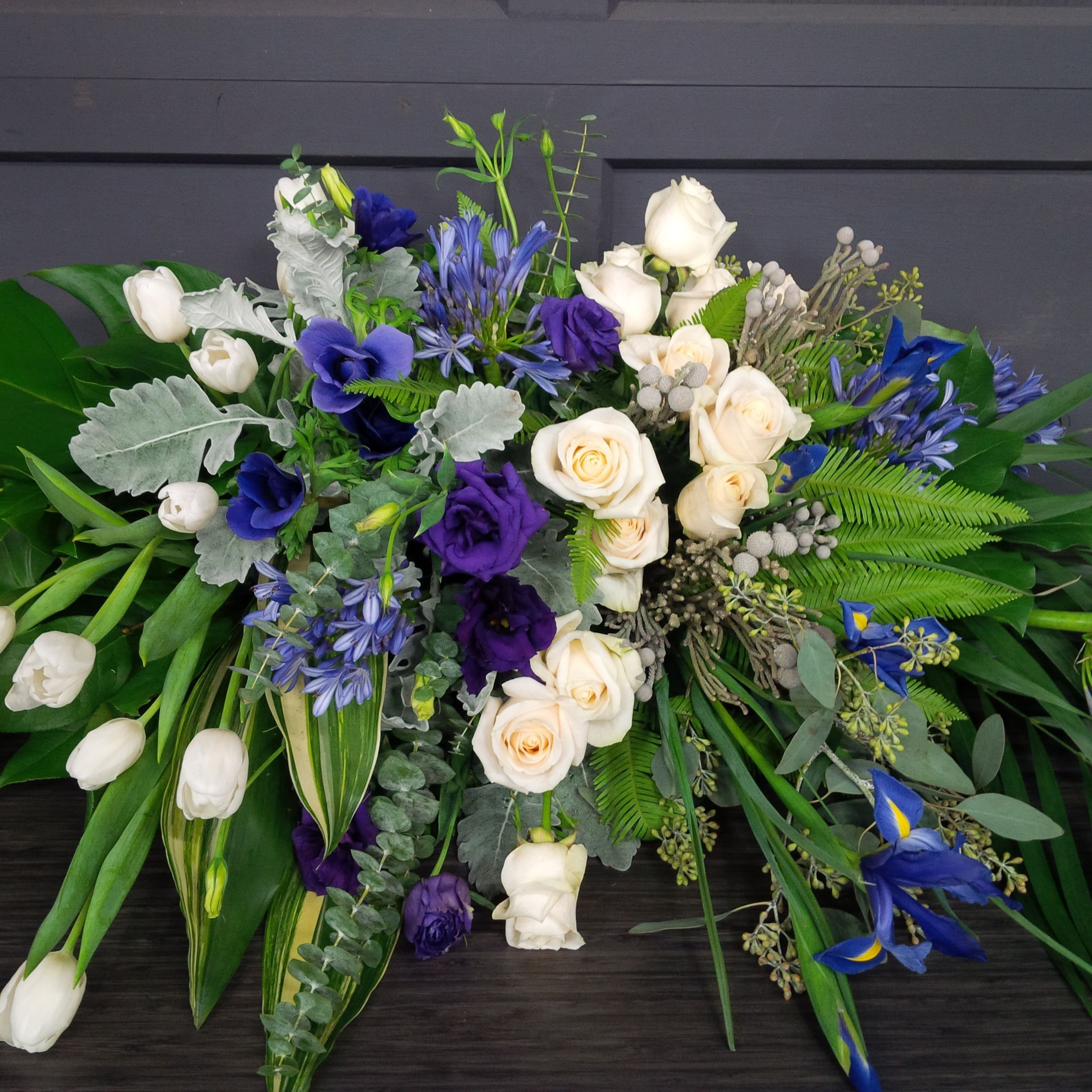 For a beloved husband a purple grey and ivory casket spray Designed by Lilies White