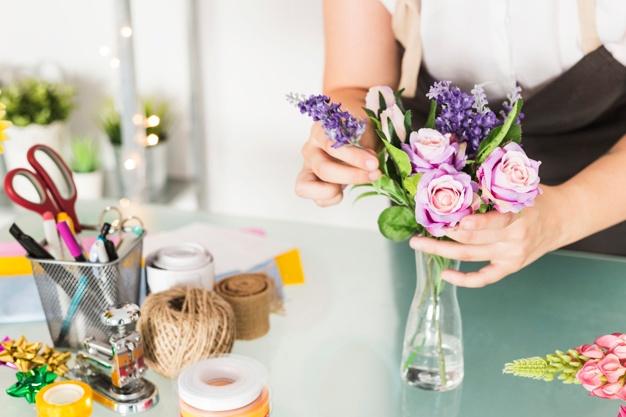 Close-up-female-florist-hand-arranging-flowers-vase-glass-desk www.freepik.com
