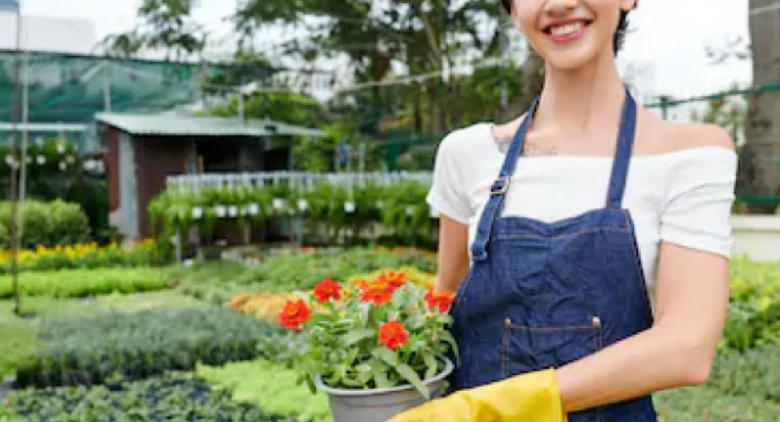 Cropped image of female florist with beautiful toothy smile holding plant she found in local outdoor nursery garden www.shutterstock.com