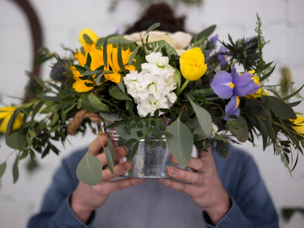 Defocused-florist-holding-flower-vase-front-his-face www.freepik.com