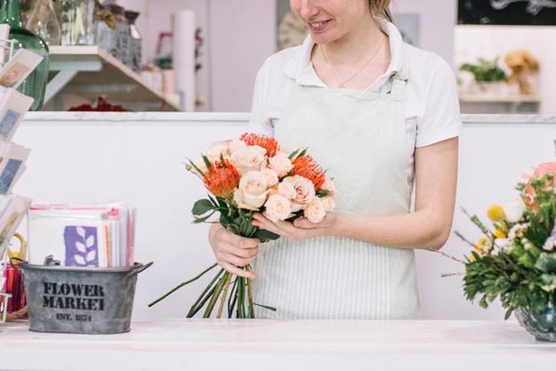 Florist-holding-bouquet-near-counter www.freepik.com