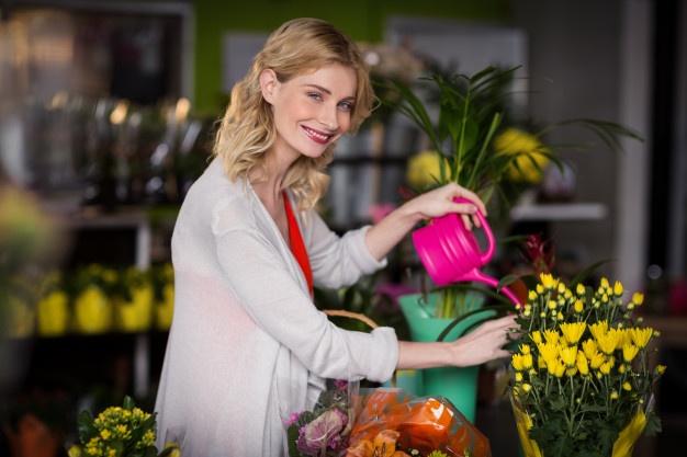 happy-female-florist-watering-flowers_freepik.com