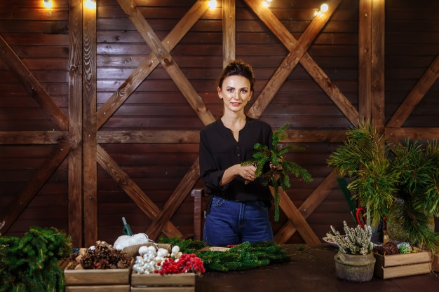 working-florist-woman-with-christmas-wreath-young-cute-smiling-woman-designer-preparing-christmas-evergreen-tree-wreath_freepik.com